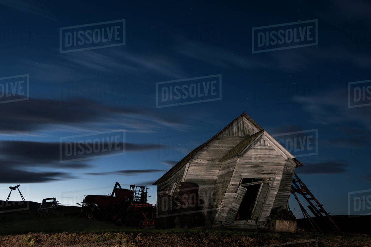 Abandoned house on field against sky at night stock photo