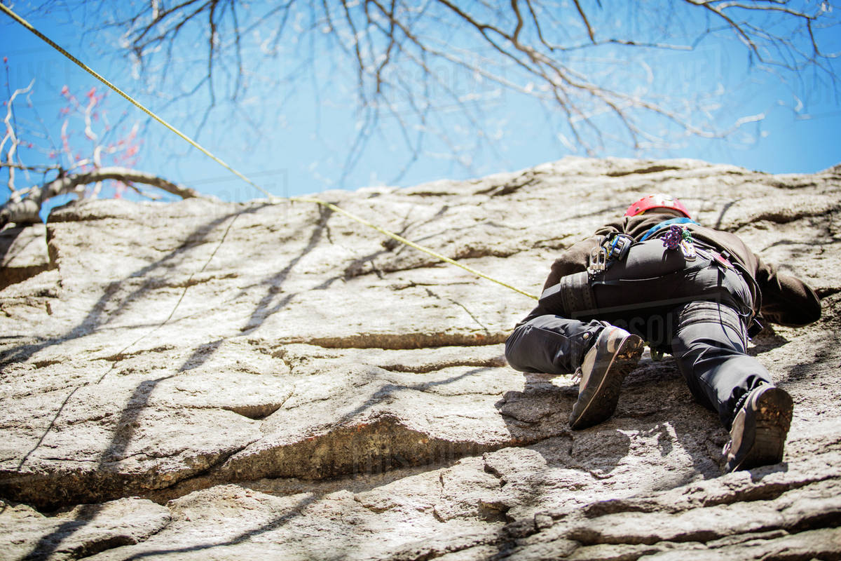 Man climbing down cliff Royalty-free stock photo