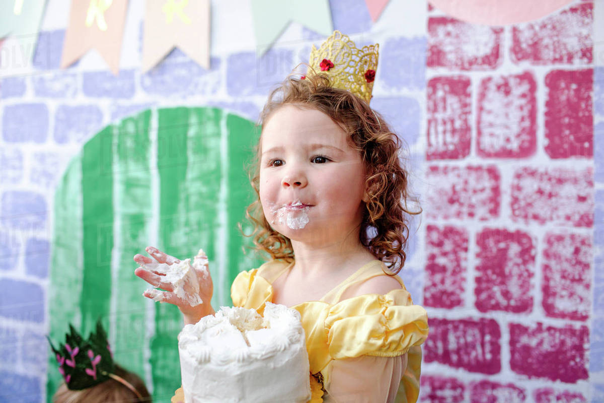 cute girl with cake standing against castle painting during princess