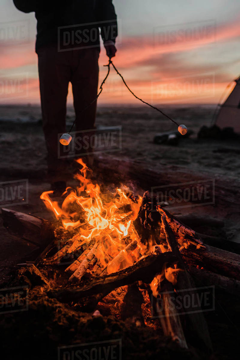 Low Section Of Man Roasting Marshmallows Over Campfire At Beach