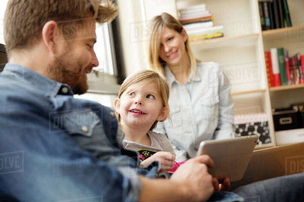 Girl looking at father holding digital tablet with woman in background Royalty-free stock photo