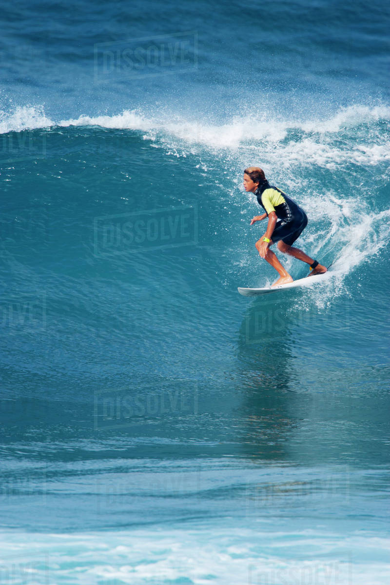Young boy(14-15) on surf board riding wave Royalty-free stock photo