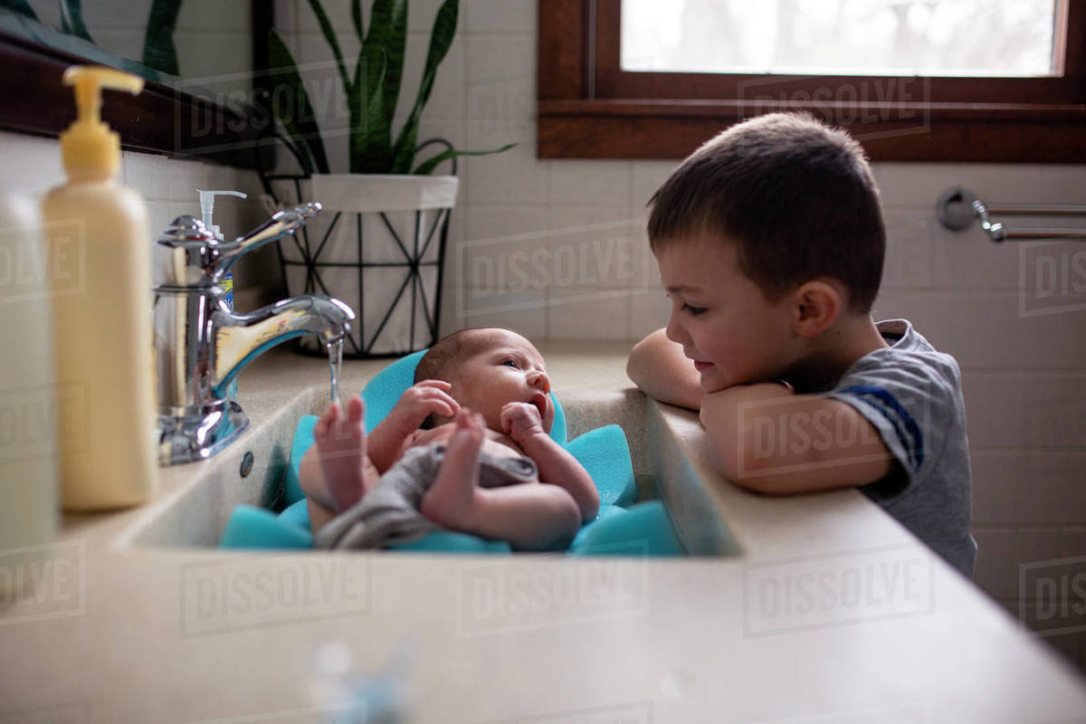 Brother looking at baby boy in bathroom sink at home - Stock Photo ...