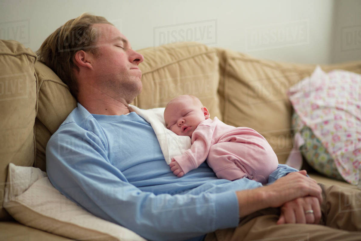Father With Baby Girl Sleeping On Sofa At Home Stock Photo Dissolve