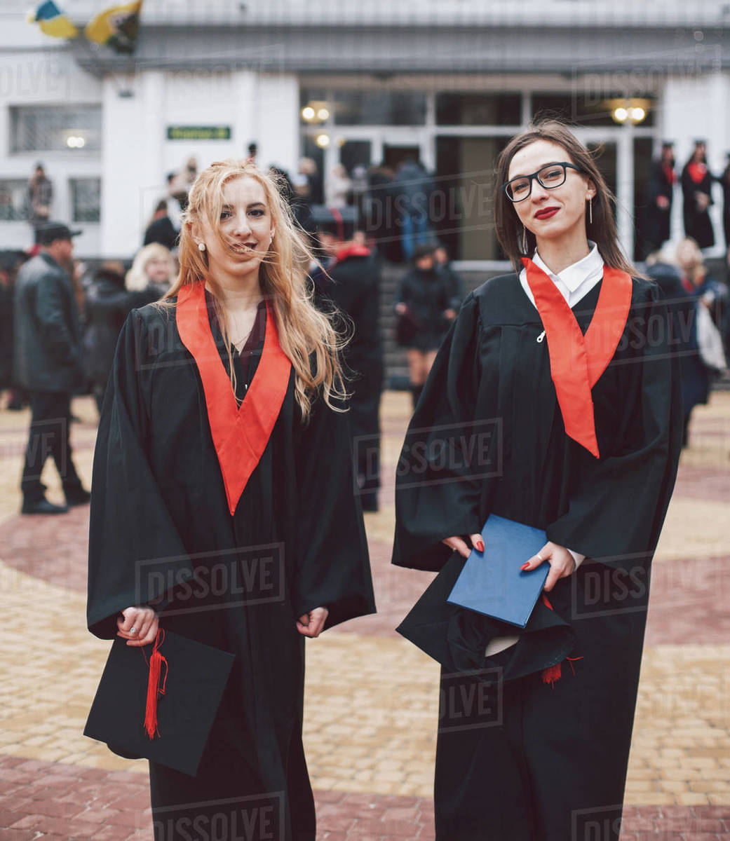 Portrait of happy female students wearing graduation gowns while ...
