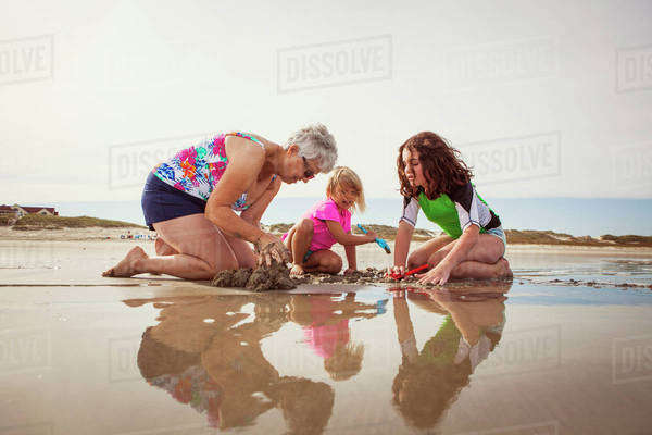 Grandmother with grandchildren (4-5,  10-11) on beach by sea Royalty-free stock photo