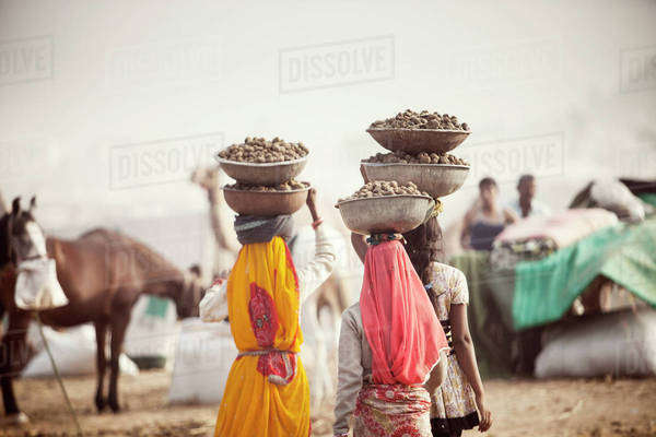Women transporting food in large bowls balanced on heads at Pushkar Camel Festival Royalty-free stock photo