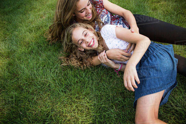 Mother and daughter enjoying while lying on grassy field at park Royalty-free stock photo