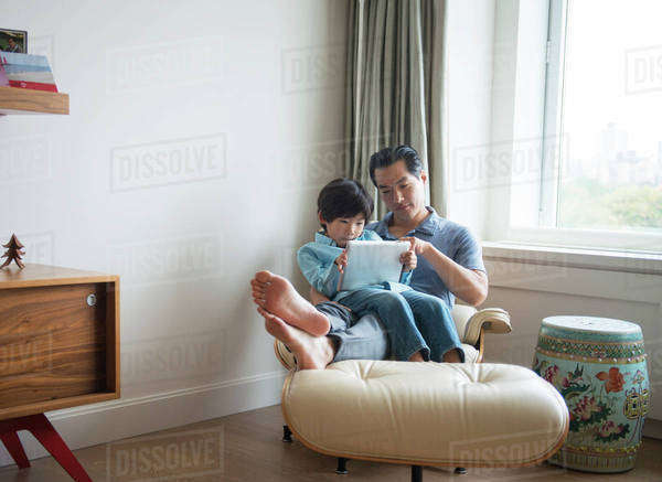 Boy surfing net with father in living room Royalty-free stock photo