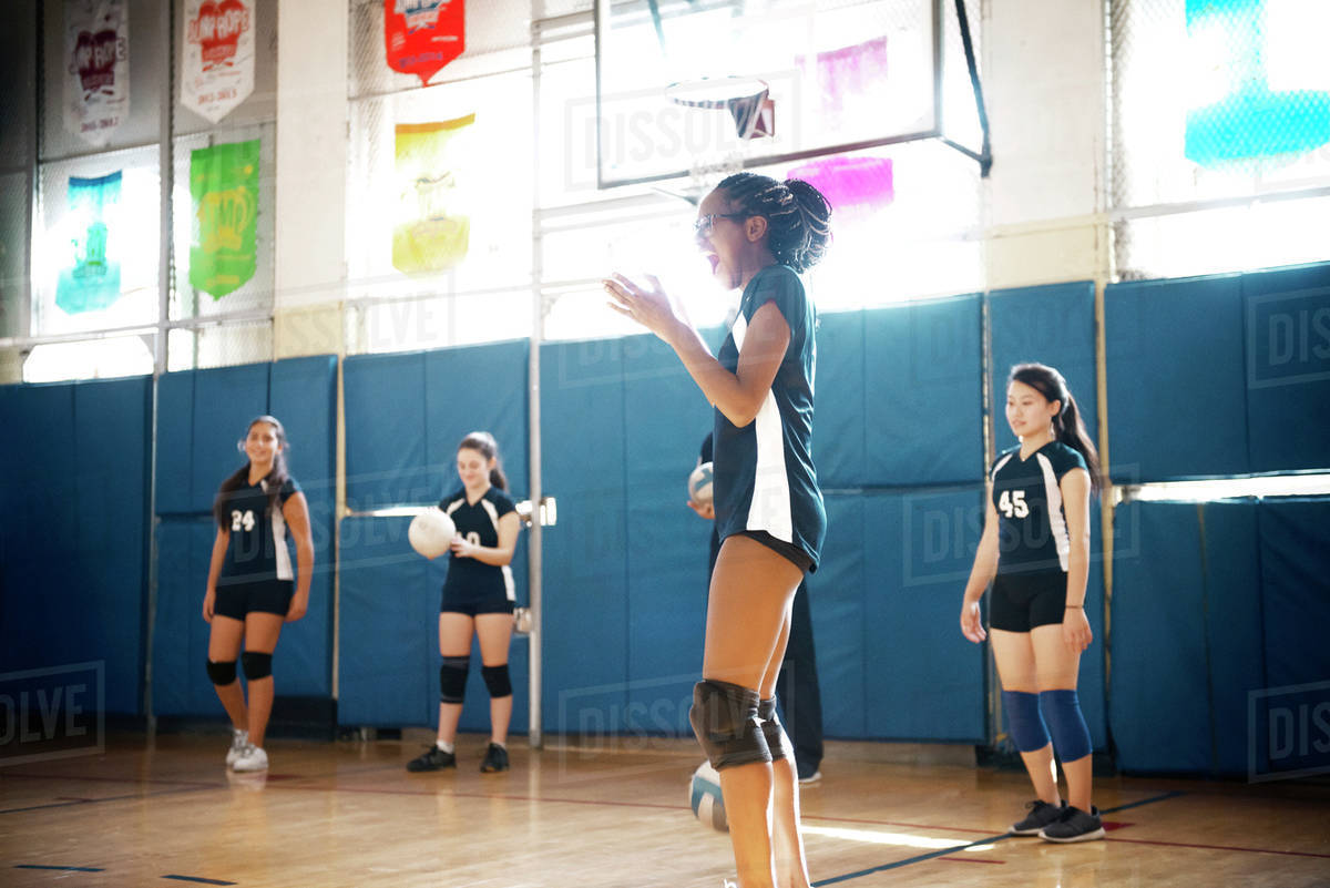 Teenage girls playing at indoor volleyball court - Stock Photo ...