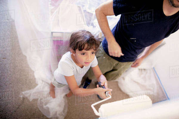 Girl standing besides father while painting wall at home Royalty-free stock photo