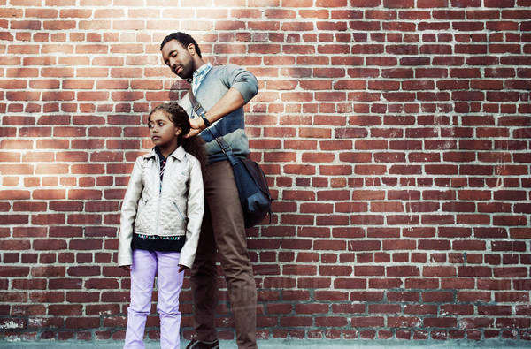 Father tying daughter's hair while standing against brick wall Royalty-free stock photo