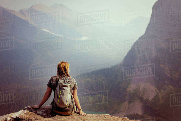 Rear view of woman sitting at cliff against valley and mountains Royalty-free stock photo