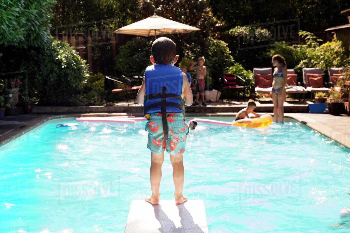 Rear view of boy standing on diving board at swimming D1061_28_692
