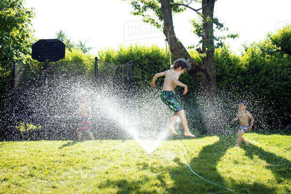 Boy jumping over water sprinkler at grassy field on sunny day Royalty-free stock photo