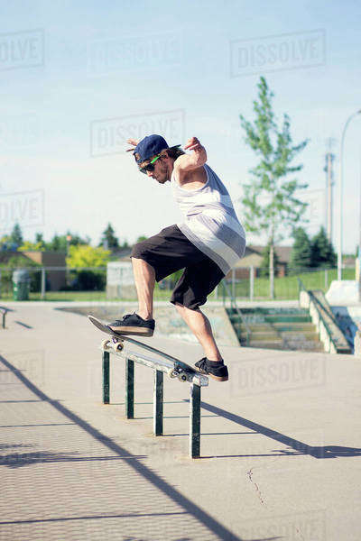 Young man balancing on railing with skateboard at park Royalty-free stock photo