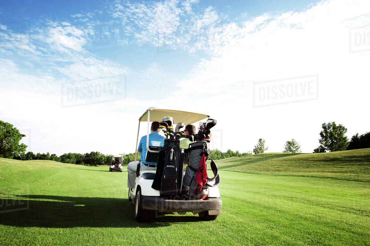 Rear view of two golfers driving cart Royalty-free stock photo