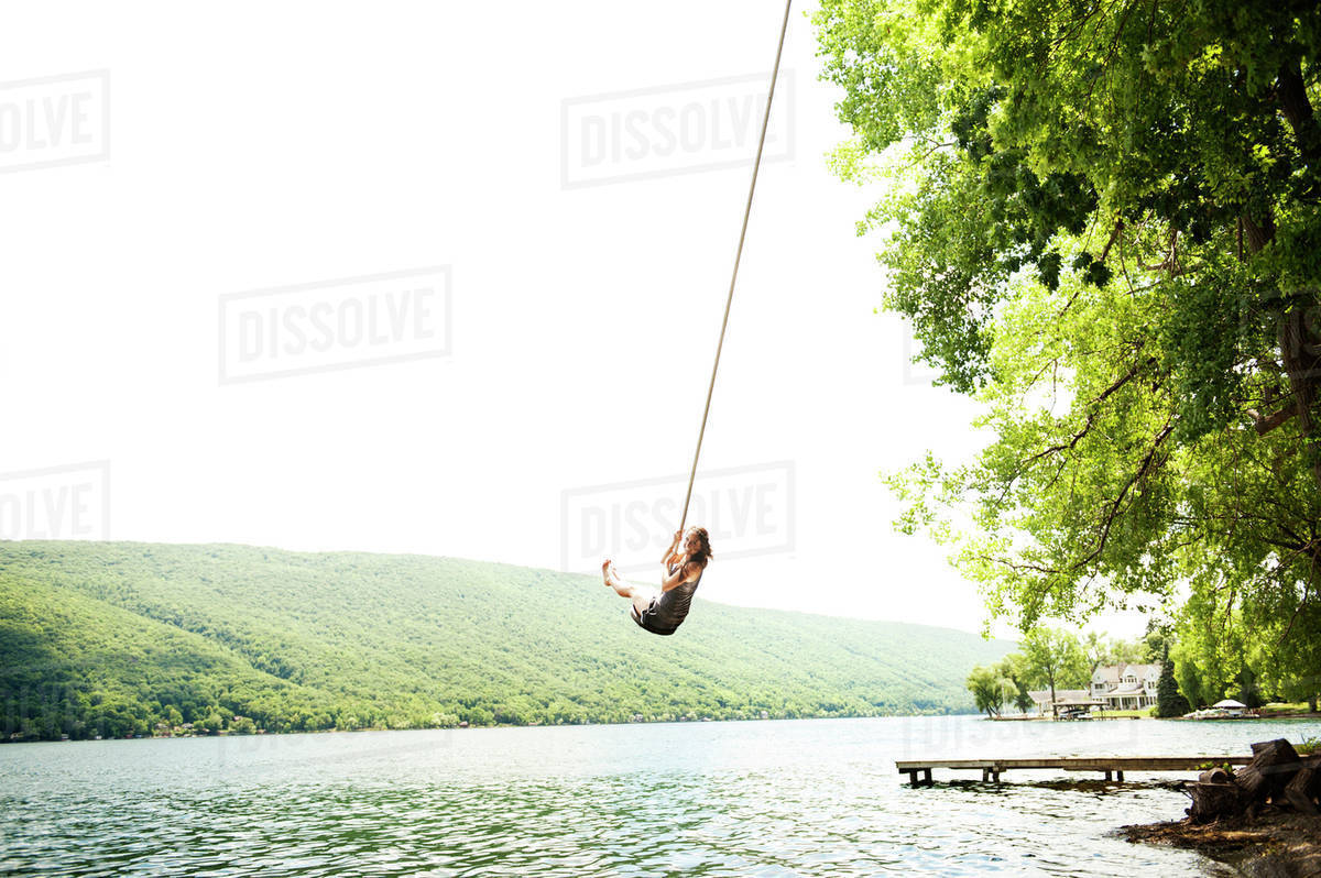Young woman on rope swing over lake Royalty-free stock photo