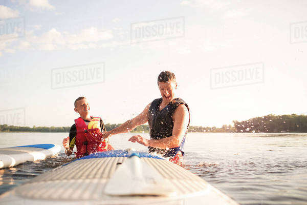 Man with son standing in lake next to paddleboards and laughing Royalty-free stock photo