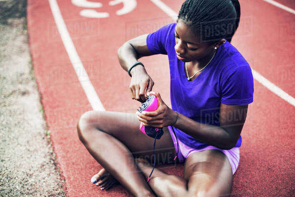 Female athlete examining shoe while sitting on running tracks Royalty-free stock photo