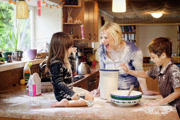 Mother with son (6-7) and daughter (2-3) cooking and laughing in kitchen Royalty-free stock photo