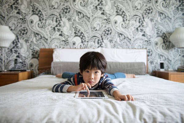 Portrait of boy (6-7) using tablet pc on bed Royalty-free stock photo