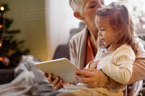 Grandmother kissing granddaughter (2-3) and using digital tablet Royalty-free stock photo