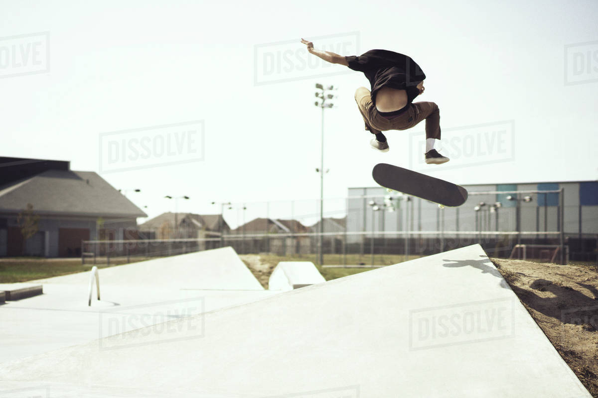 Rear view of man jumping with skateboard on ramp at park against clear sky Royalty-free stock photo