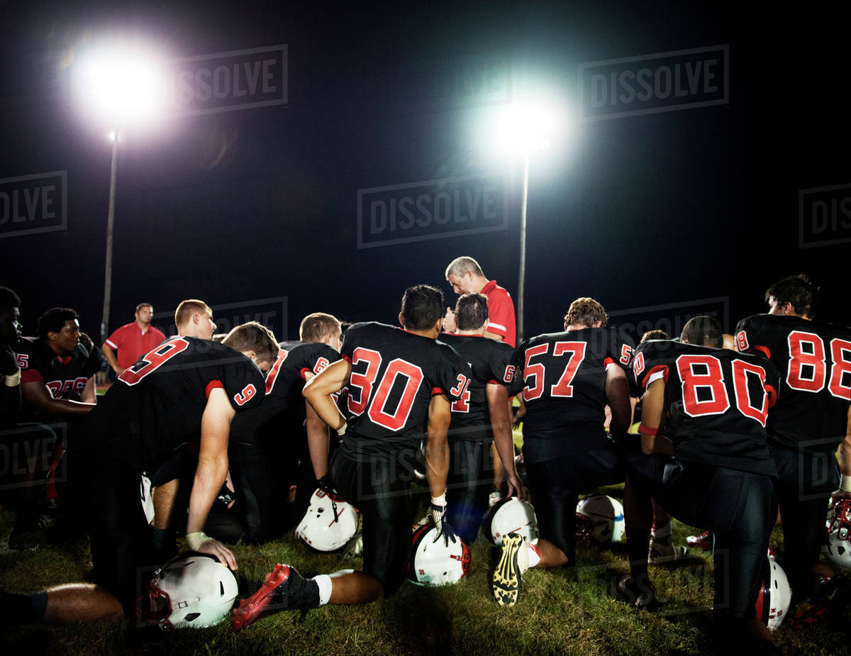 Football players (14-15, 16-17) with coach on playing field Royalty-free stock photo