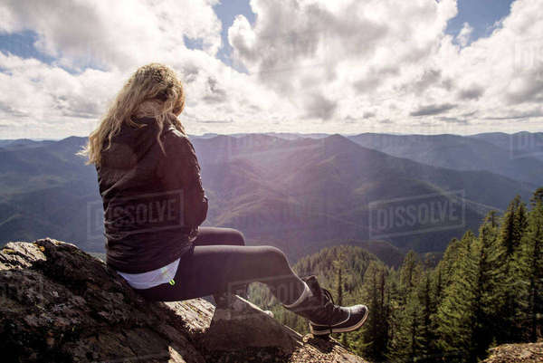 Woman sitting on rock at mountain cliff against cloudy sky Royalty-free stock photo