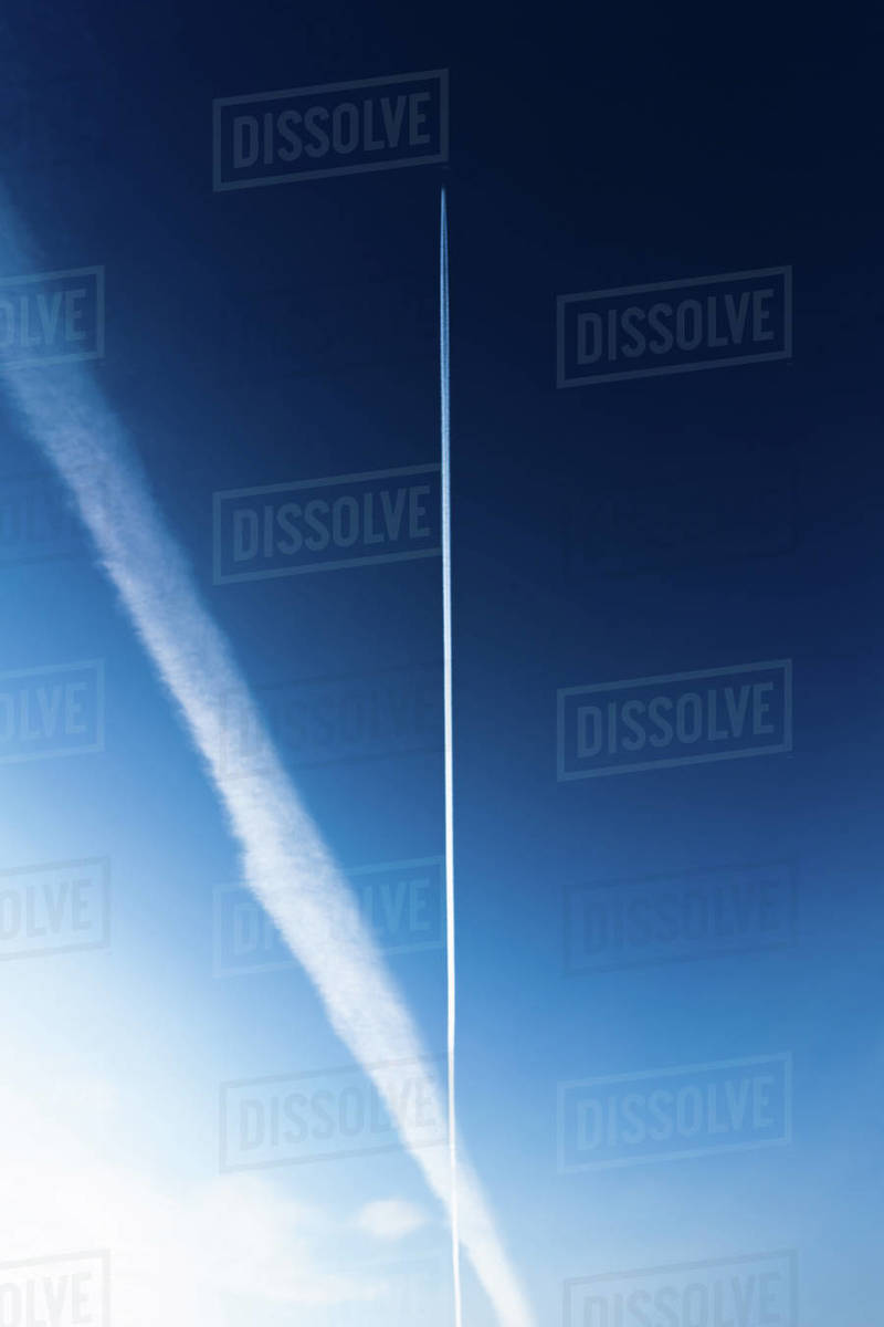 Chem trails from an airplane cross across a blue sky Royalty-free stock photo
