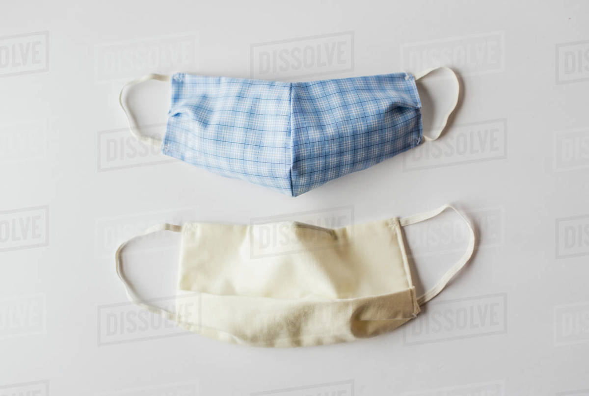 Homemade cloth face masks used during Covid-19 on white backdrop. Royalty-free stock photo