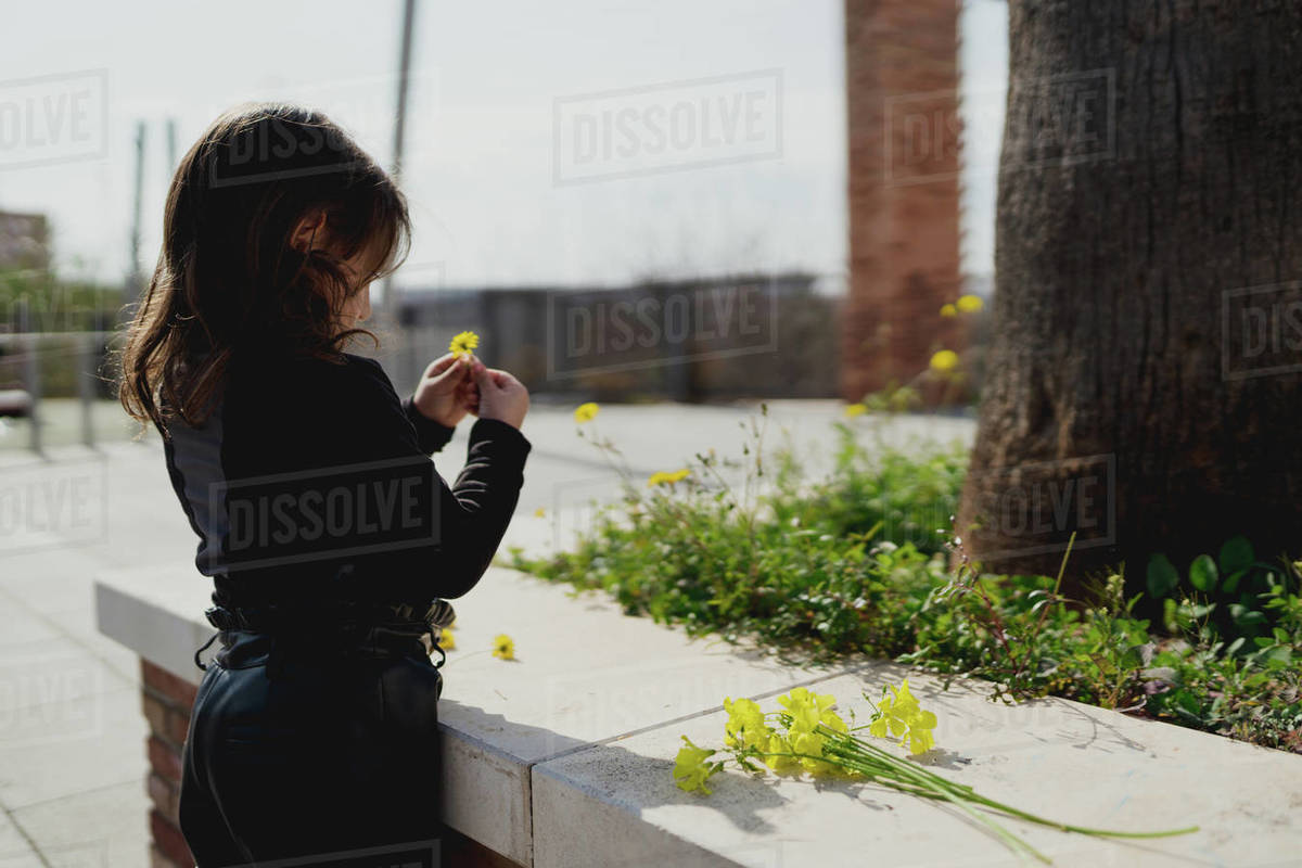 Adorable four-year-old girl looking at the yellow flowers in her hand Royalty-free stock photo