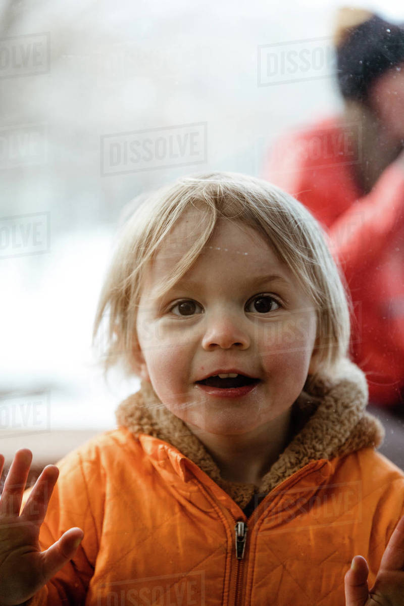 3 year old girl smiles through window at her uncle during quarantine Royalty-free stock photo