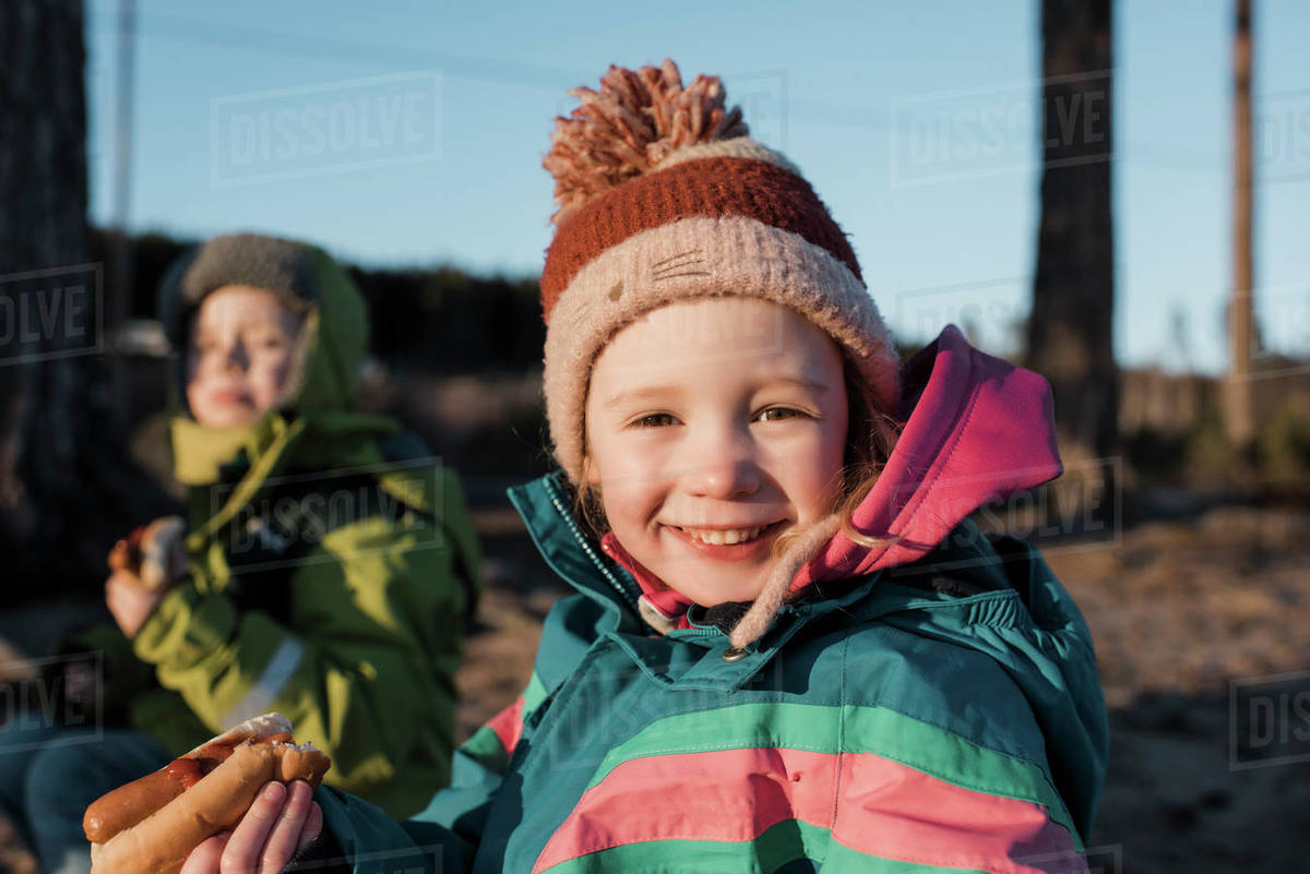 Portrait of a young girl eating a hot dog by a campfire in Sweden Royalty-free stock photo