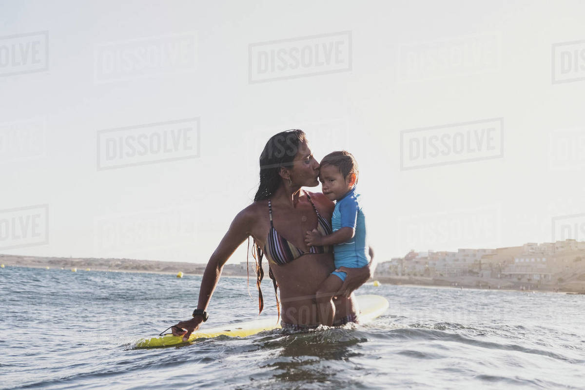 Portrait of a surfer mother holding her son next to a surfboard in sea Royalty-free stock photo