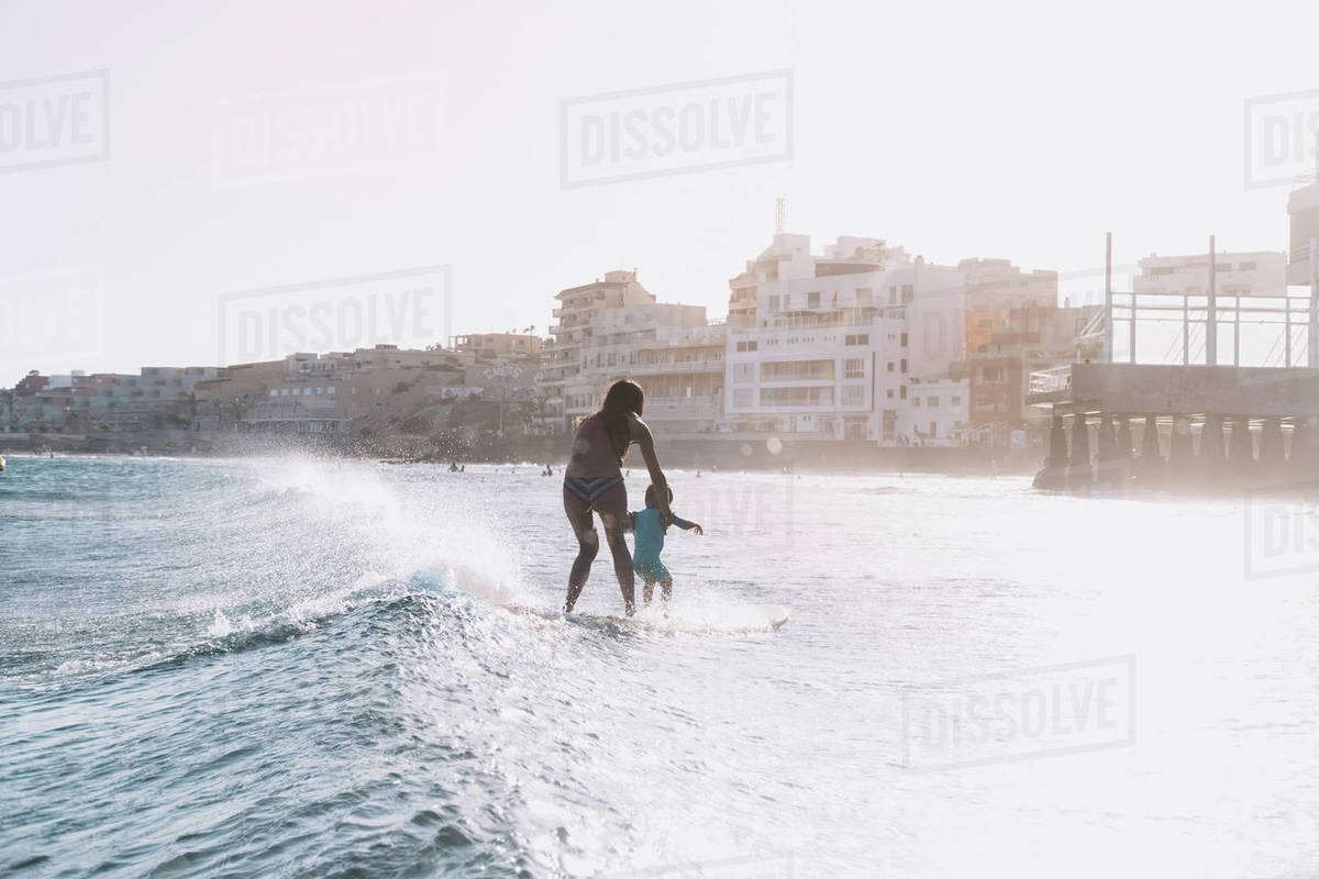 Pulled back view of mother and son surfing a small wave at sea Royalty-free stock photo