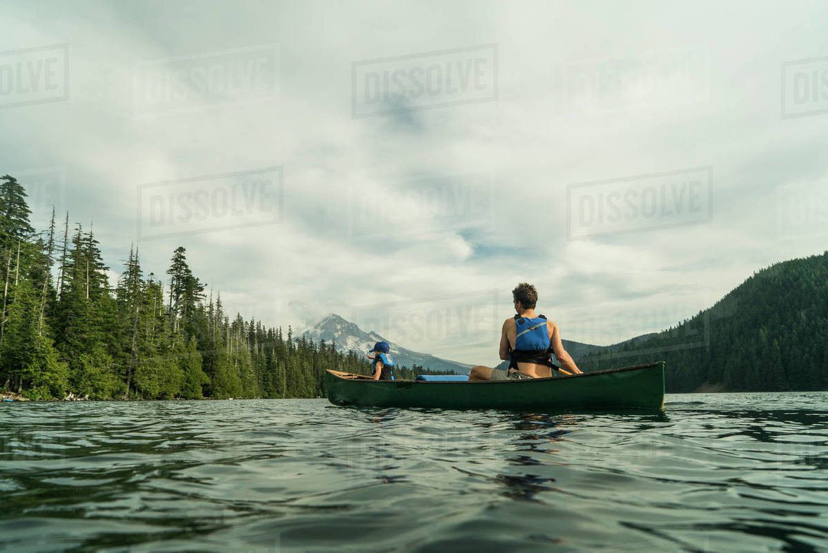 A young girl rides in a canoe with her dad on Lost Lake in Oregon. Royalty-free stock photo