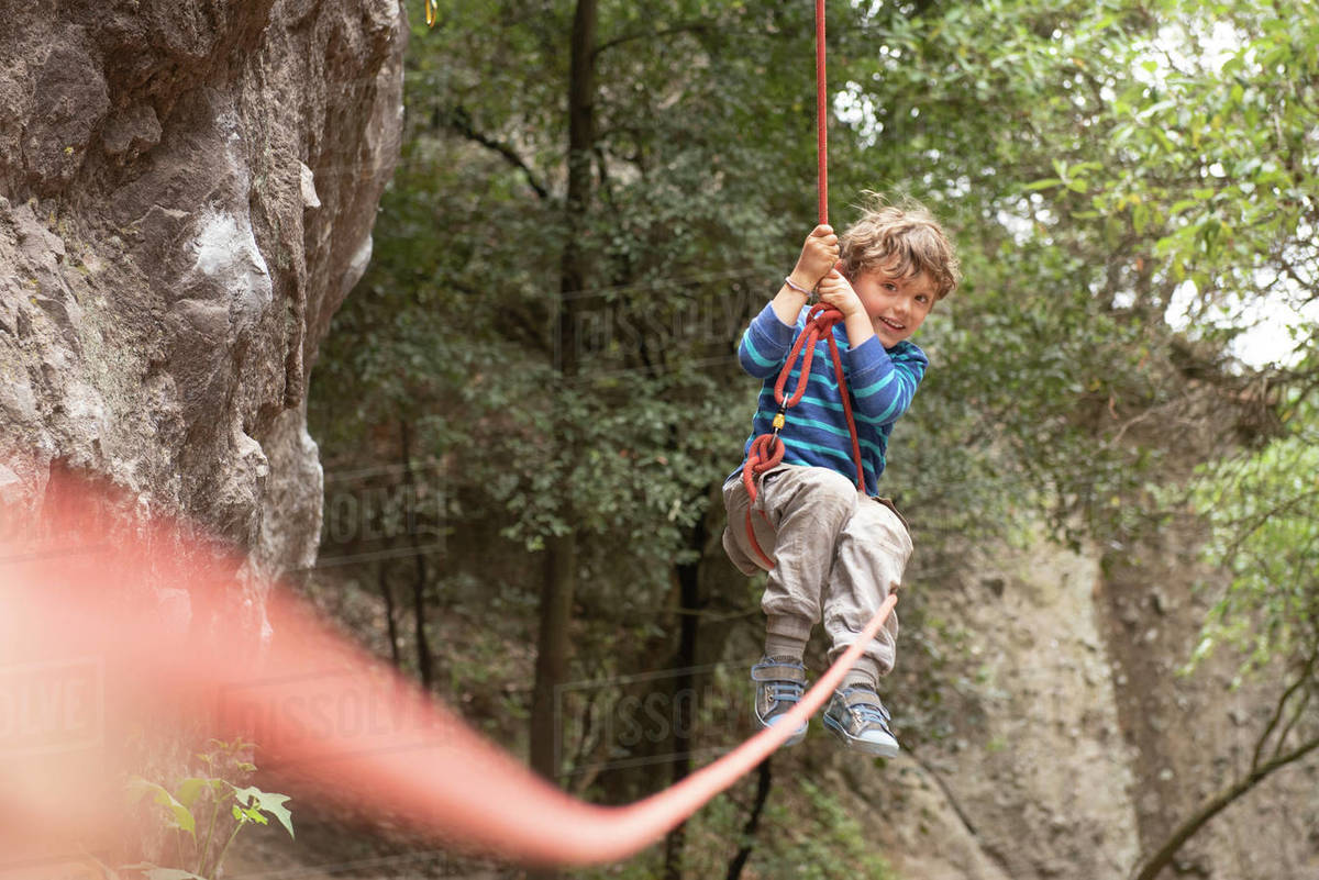 Four year old toddler swings hanging from a climbing rope Royalty-free stock photo