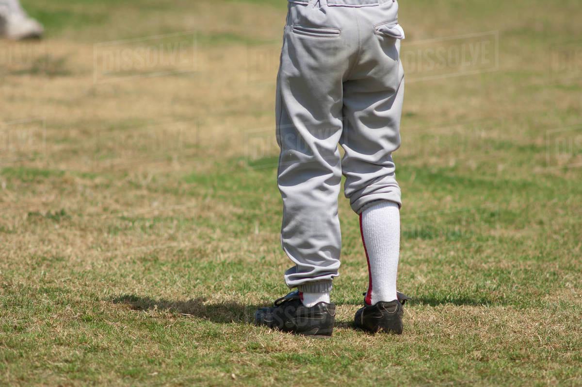 Boys legs wearing uneven baseball pants Royalty-free stock photo