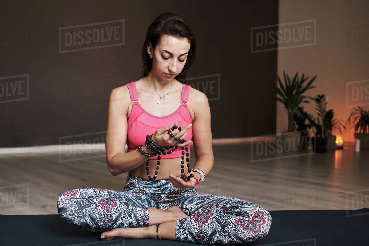 Young woman meditating alone with a yoga studio for yoga with beads Royalty-free stock photo