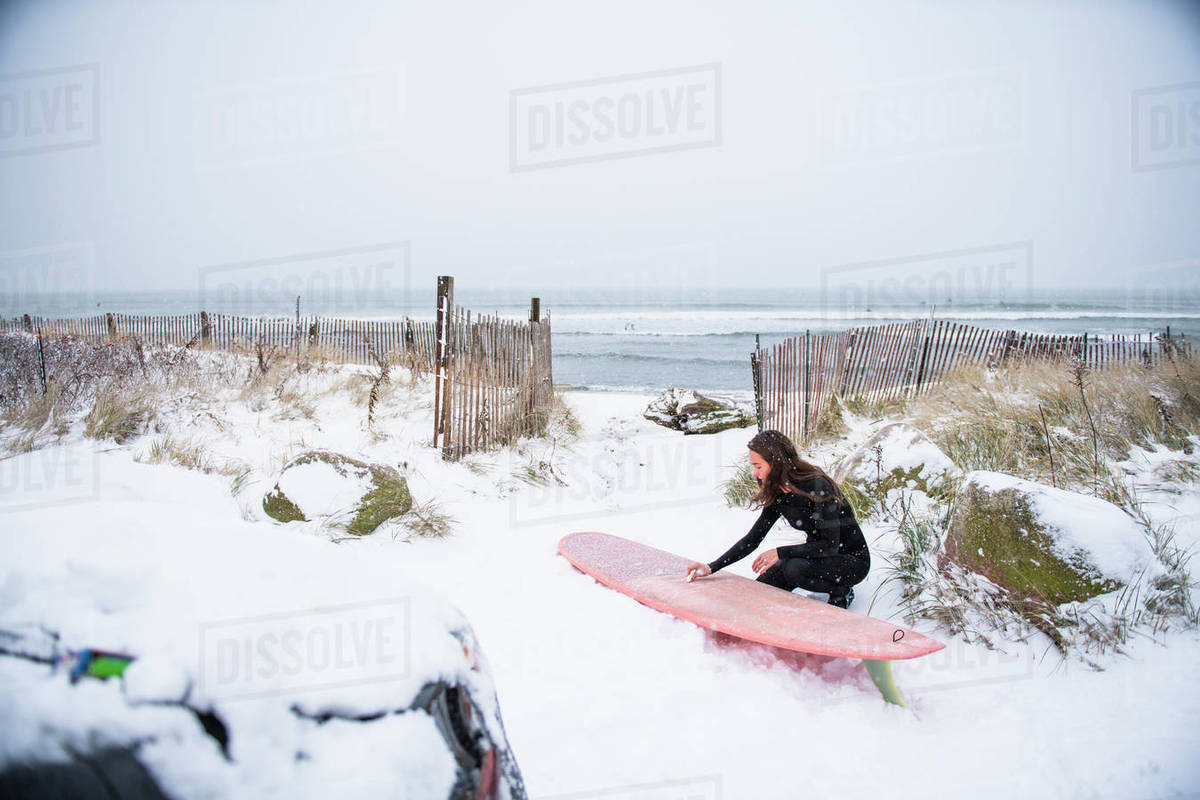 Woman going surfing during winter snow Royalty-free stock photo