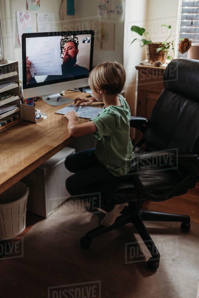 Elementary age boy taking online class from teacher during isolation Royalty-free stock photo