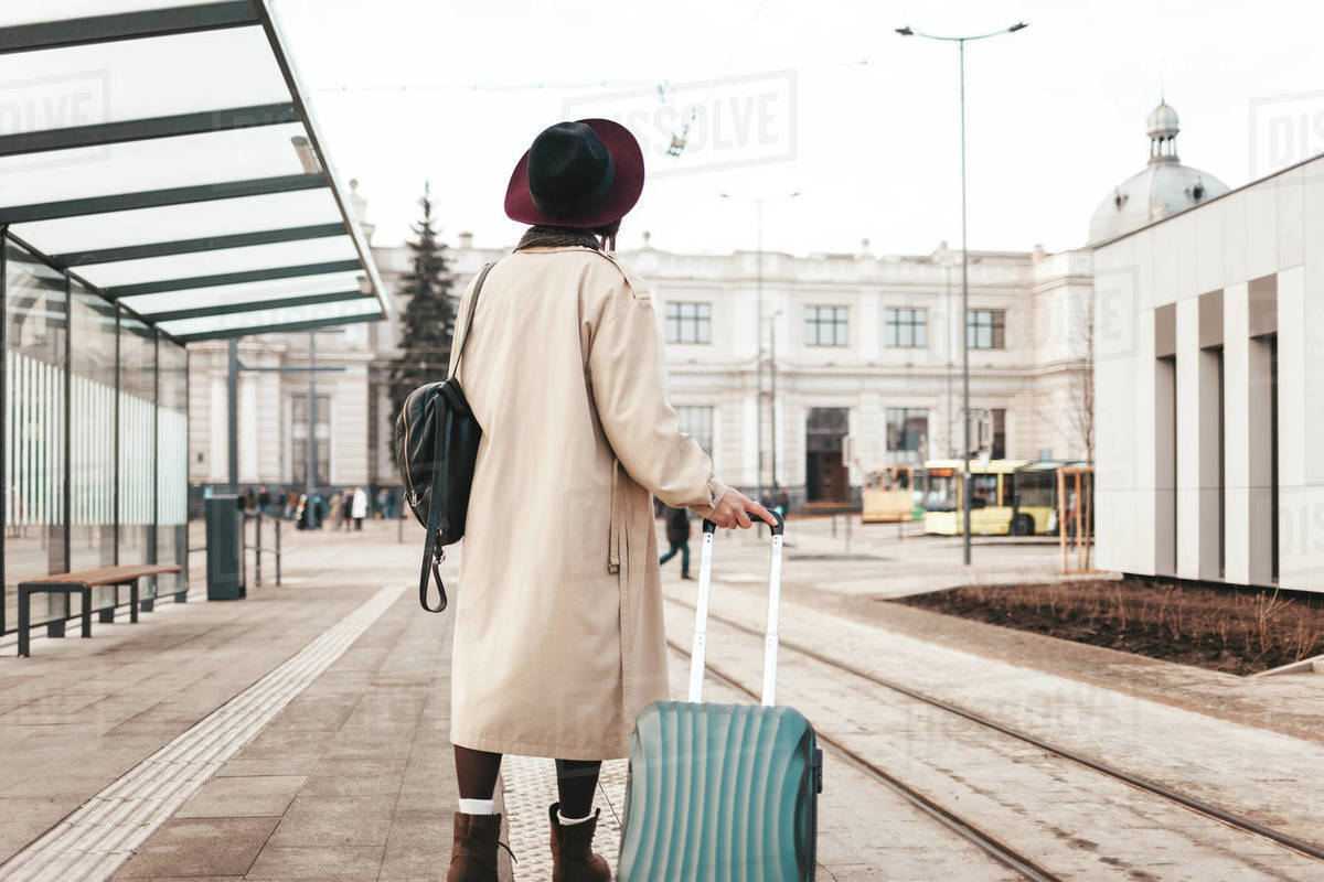Stylish girl with a suitcase stands at a city stop awaiting a tram Royalty-free stock photo