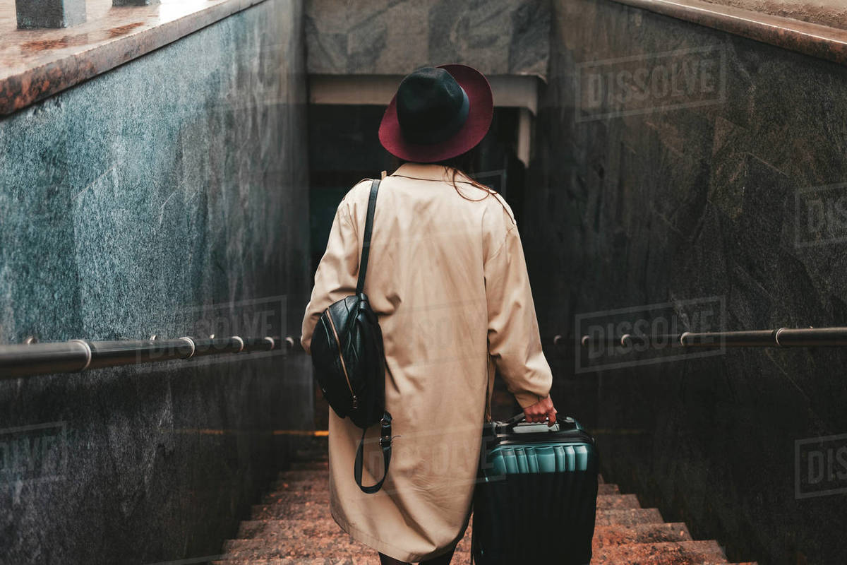 Stylish woman with a suitcase get down the stairs of the train station Royalty-free stock photo
