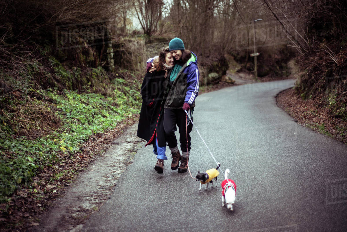 Gay female couple laugh and walk dogs up country road in czech winter Royalty-free stock photo