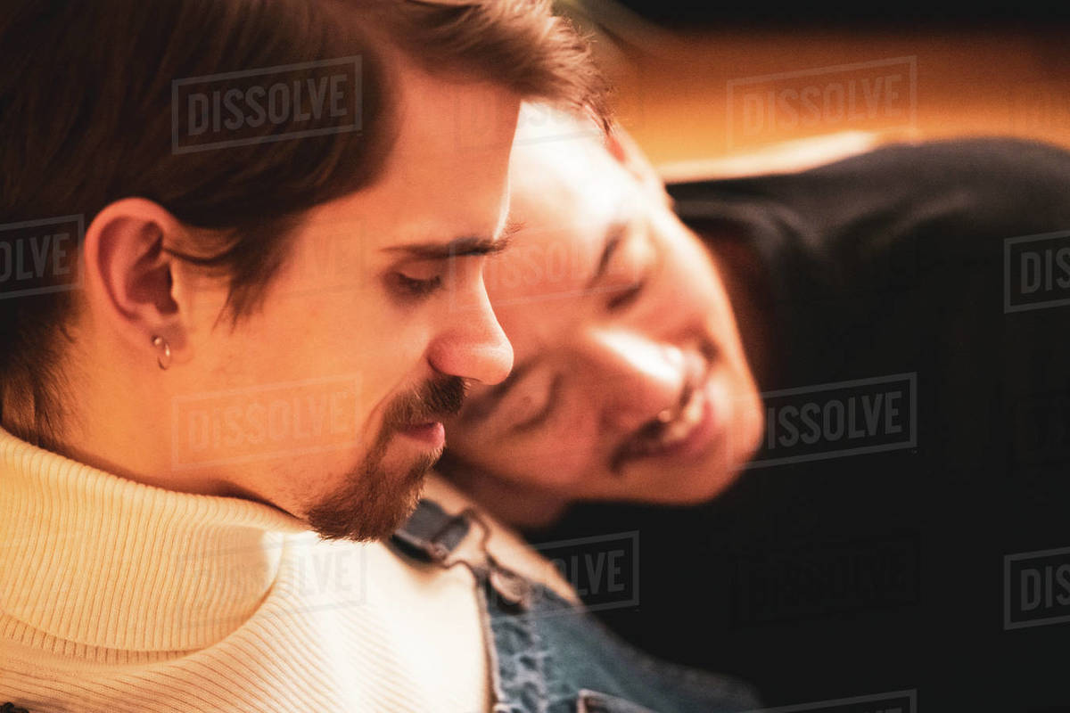 Gay male inter-racial couple cuddle and smile relaxing at home Royalty-free stock photo