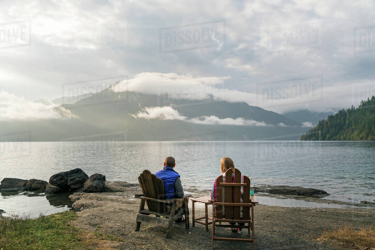 Man and woman sitting at edge of lake during sunset Royalty-free stock photo