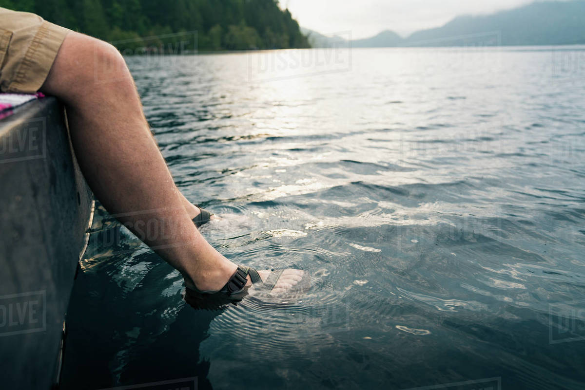 Man's feet in sandals dipped into lake Royalty-free stock photo