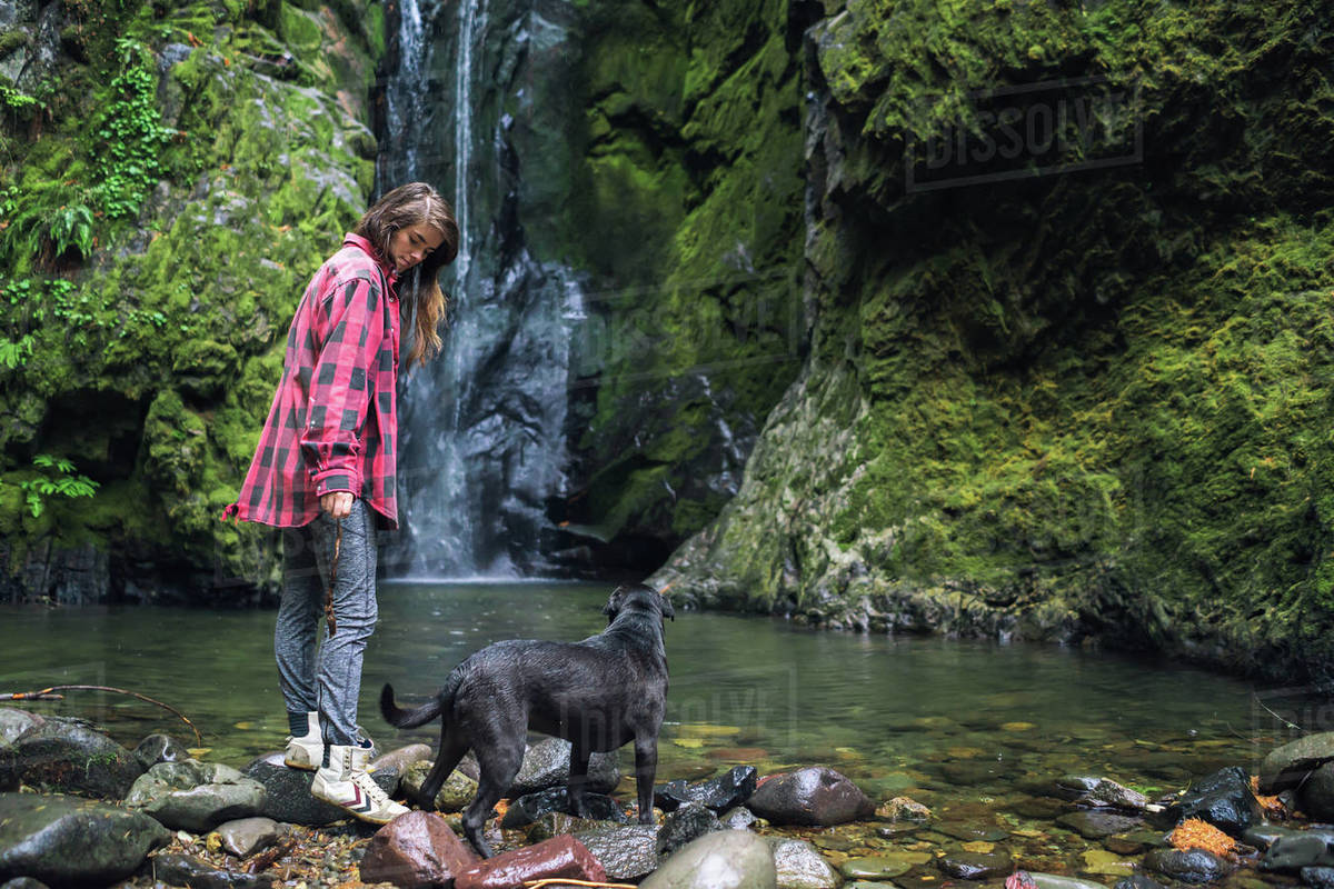 Young woman looking down at dog near waterfall Royalty-free stock photo
